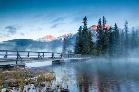 First glimpse of a golden sunrise on a misty and foggy morning at Pyramid Lake in Jasper National Park, Alberta, Canada. The wooden bridge leads to Pyramid Island on the lake.
