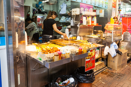A street vendor selling popular snacks at Fa Yuen Street market in Kowloon. These include stinky tofu, pig intestines, fishballs, beefballs and seafood served on skewers and dipped in a variety of sauces.