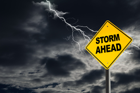Storm Ahead warning sign against a dark, cloudy and thunderous sky. Concept of political storm, personal crisis, or imminent danger ahead.