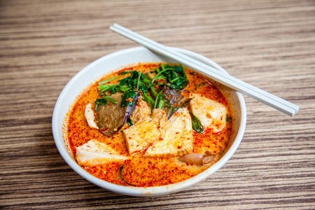 Photo pour A bowl of Singapore Laksa Yong Tau Foo, a popular local dish served in spicy curry shrimp paste gravy soup base with coconut milk; tofu and eggplant filled with fish paste; vegetables; cutterfish and fishball over thick noodles underneath. This is a favor - image libre de droit
