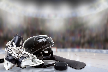 Photo pour Low angle view of hockey helmet, skates; stick and puck on ice with deliberate shallow depth of field on brightly lit stadium background and copy space. - image libre de droit
