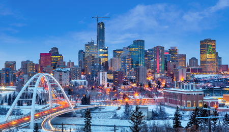 Photo for Edmonton downtown Winter skyline just after sunset at the blue hour showing Walterdale Bridge across the frozen, snow-covered Saskatchewan River and surrounding skyscrapers. Edmonton is the capital of Alberta, Canada. - Royalty Free Image