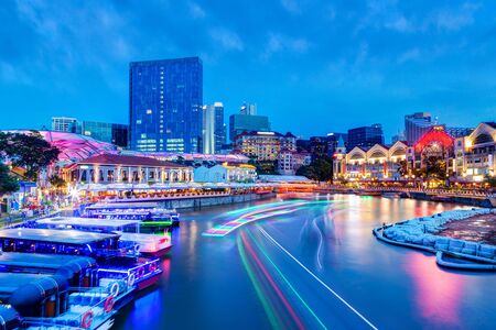Photo for Sunset night life at Clarke Quay on Singapore River as colorful light trails from river boats and surrounding bars and restaurants light up the popular tourist area that used to be a commercial warehouse center during the colonial era. - Royalty Free Image
