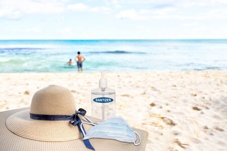 Vacationing in the New Normal after COVID-19 coronavirus pandemic. Tourism concept showing lounge chair on sandy beach with beach hat, hand sanitizer, medical face mask and copy space.