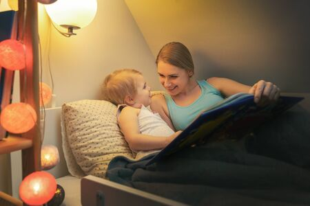 Photo pour mother reading fairy tail book to her child in the evening before sleep at home - image libre de droit