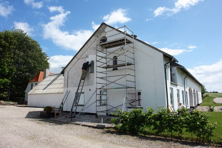 Man on scaffolds painting a house during exterior renovations