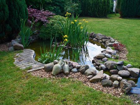 Photo pour Beautiful classical garden fish pond surrounded by grass gardening background - image libre de droit
