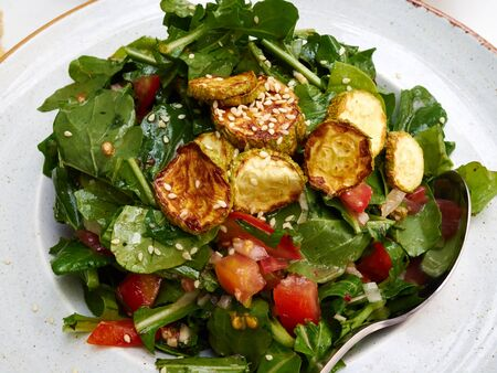 Photo for Healthy eating ! Fresh organic green Salad with fried zucchiniand juicy tomatoes on a plate - Royalty Free Image