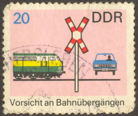 The scanned stamp. German stamp. The car on a railway crossing.