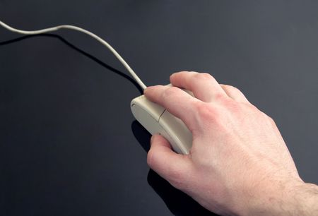 man's hand holding computer mouse, black reflective background