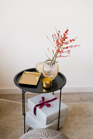 Photo pour A coffee table with a gold tray, branches with red berries in a glass vase and gift boxes with ribbons and a bow on it - image libre de droit