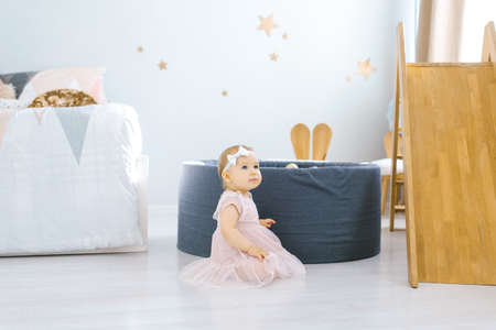Photo pour Little girl 1 year old sits on the floor in the children's room - image libre de droit