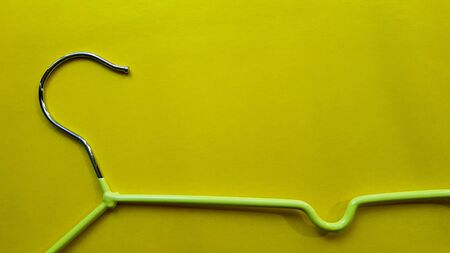 Hanger for clothes on a yellow background. Green hanger. Background with copy space. Black friday, shopping day.