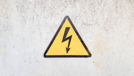 Photo pour Danger sign of high voltage electricity. Yellow triangular sign with a lightning in the center. This warning is written on an old metal surface painted with gray paint - image libre de droit