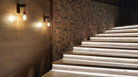 Photo for Illuminated staircase with wooden steps and illuminated at night in the interior of a large house. - Royalty Free Image