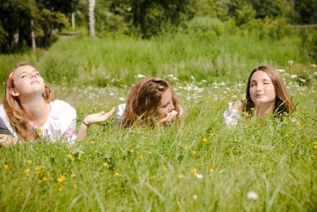 Three teen friends lying in green grass
