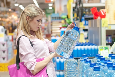 Beautiful young woman buys a huge bottle of water in the store
