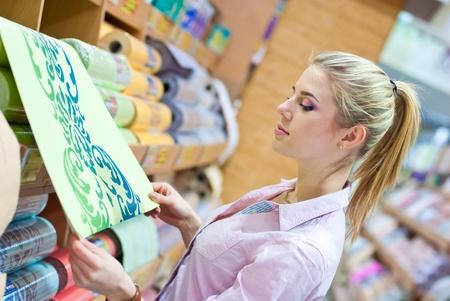 Photo pour Young beautiful blond woman choosing among rolls of wallpaper in shop - image libre de droit