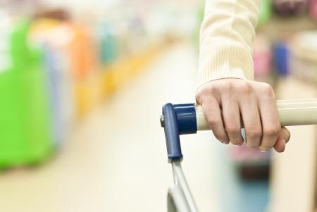 Woman shopping in super market and pushing cart hand closeup