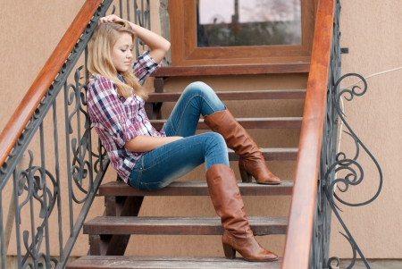 Pretty happy teenage girl woman female sitting on the stairs on sunny autumn day in cowboy hat