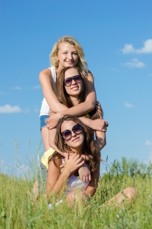 Photo pour Three happy teen girls sitting on green grass and embracing against blue sky on bright summer day - image libre de droit