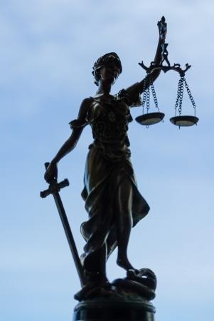 Femida bronze goddess statue holding scales over blue sky