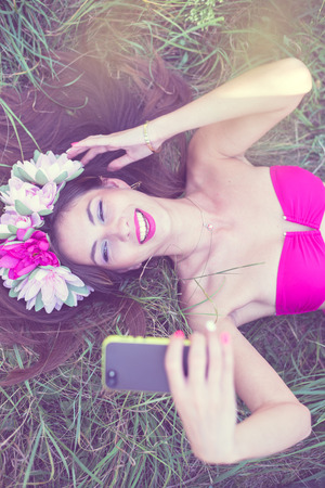 filtered image of beautiful brunette young lady in pink bikini and flower crown having fun making selfie picture lying on green grass outdoor