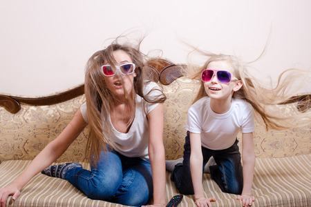 Young beautiful woman with blond little girl sitting in 3D glasses on sofa