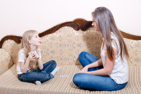 Picture of young pretty woman and little girl playing cards