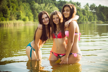 Three beautiful teenage girls in swimsuits standing in water outdoorsの写真素材