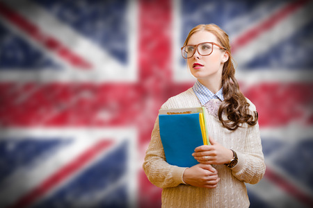 Picture of young woman in glasses and sweater holding files. Student girl on english union jack blurred background