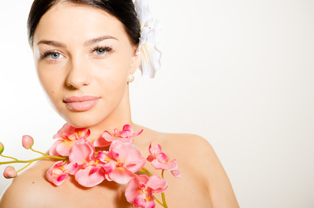 Adult woman with beautiful face and white flowers. Skin care concept.