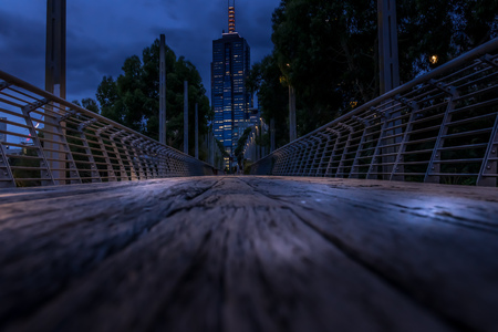 Wooden pedestrian bridge at night, with city scape in the background. Melbourne city.