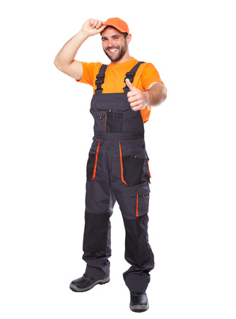 Portrait of smiling worker in blue uniform with hands doing ok gesture isolated on white background