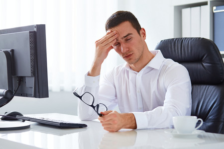 Young businessman under stress with headache and migraine