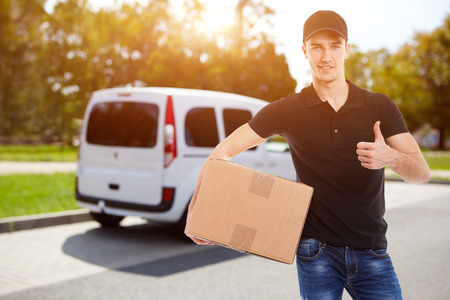 Photo pour Smiling delivery man holding a cardboard box in sunlight - image libre de droit