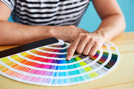 Graphic designer choosing a color from the sampler