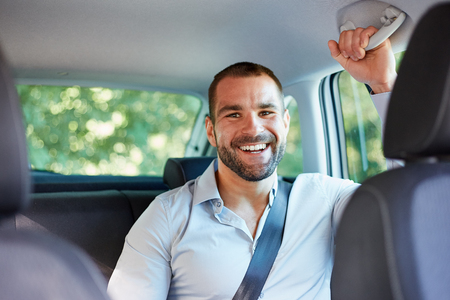 Young cheerful businessman sitting in a car