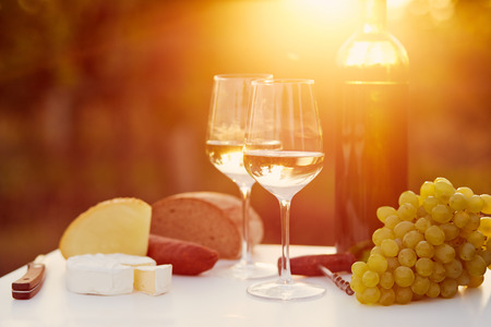Two glasses of white wine with food at sunset, toned