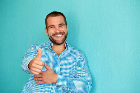 Photo pour Happy man with thumb up on a turquoise background - image libre de droit
