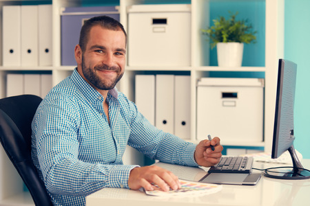 Happy graphic designer working on digital tablet, toned