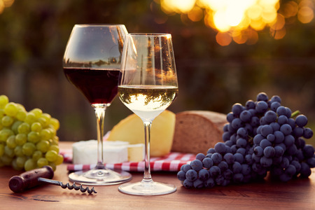 Photo for Two glasses of white and red wine with food at sunset, toned - Royalty Free Image