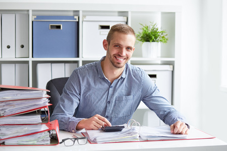Photo for Smiling businessman calculates taxes at desk in office - Royalty Free Image