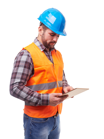 Photo pour Manual worker in blue helmet and shirt using a digital tablet, isolated on white. - image libre de droit