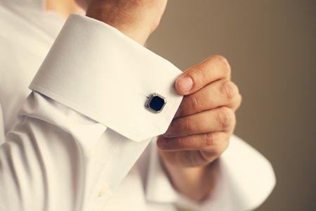 Man correcting the sleeve of his shirt, close up. Toned