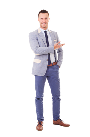 Smiling man in blue jacket showing empty copyspace, isolated on white background