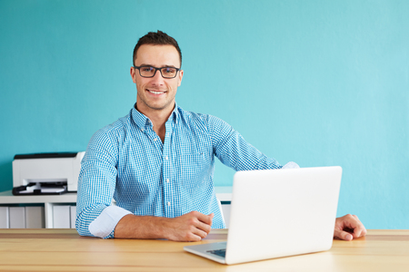 Foto de Smiling man working in modern office on computer - Imagen libre de derechos