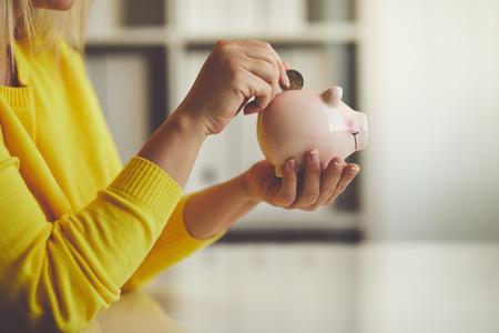 Photo pour Woman inserts a coin into a piggy bank, toned image - image libre de droit