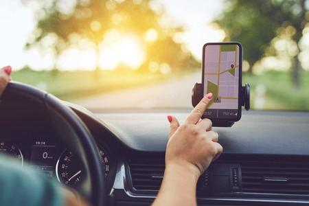 Photo pour Close-up of woman using GPS navigation in mobile phone while driving car at sunset - image libre de droit