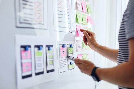 Photo pour Web developer planning application for mobile phone on whiteboard - image libre de droit